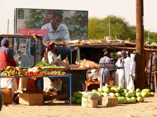 Melouny a ostatni produkty na trhu ve meste Karima pobliz Jebel Barkal. V pozadi reklama na mobilniho operatora