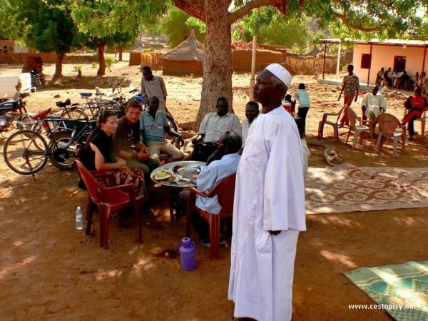 Nacelnik Mohamad Rahal na sve hostine-V pozadi obrovsky tac se specialitami s hosty okolo a deky na kterych se sedi a debatuje